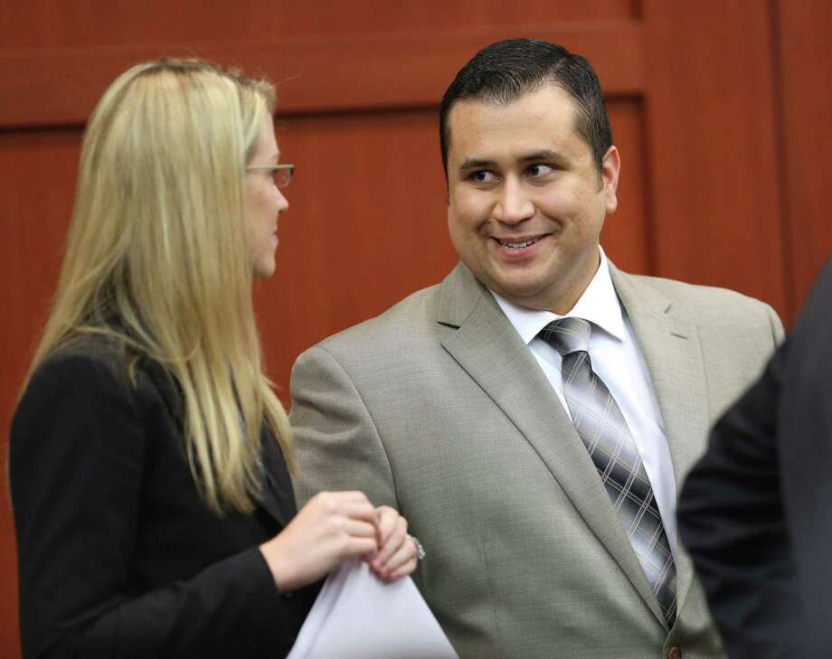 George Zimmerman chats with one of the assistants from his defense team on Tuesday. Photo: Joe Burbank, Getty Images