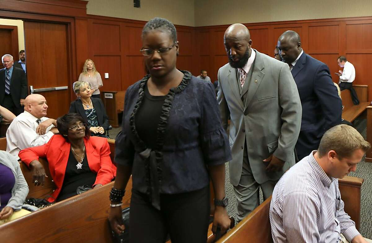 Trayvon Martin's parents, Sabrina Fulton, standing left, and Tracy Martin, center, and their attorney Daryl Parks, arrive in the courtroom for George Zimmerman's trial in Seminole circuit court in Sanford, Fla. Wednesday, July 10, 2013. Zimmerman has been charged with second-degree murder for the 2012 shooting death of Trayvon Martin.(AP Photo/Orlando Sentinel, Gary W. Green, Pool)