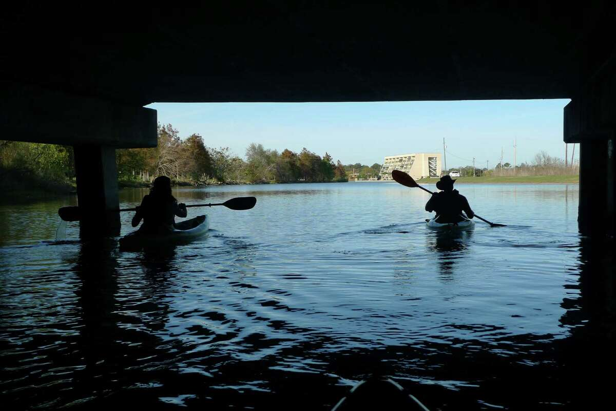 Two kayakers paddle out from under Highway 610 on Bayou St. John in New Orleans.