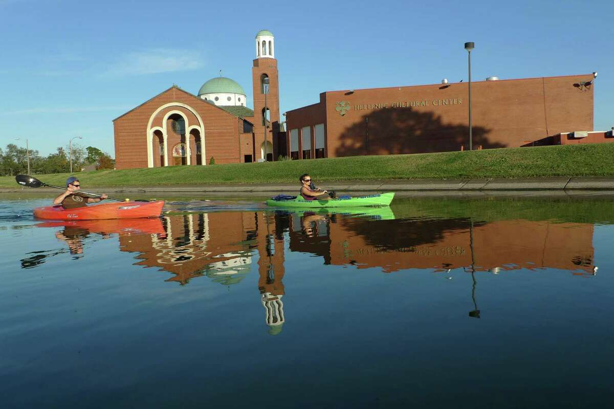 Kayakers paddle through the reflection of Holy Trinity Greek Orthodox Cathedral in Mid-City New Orleans.