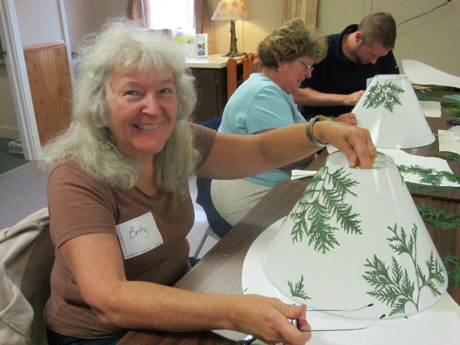 Bettey Schreiner shows off the botanical lampshade she made at the Adirondack Folk School in Lake Luzern. (Adirondack Folk School Staff)