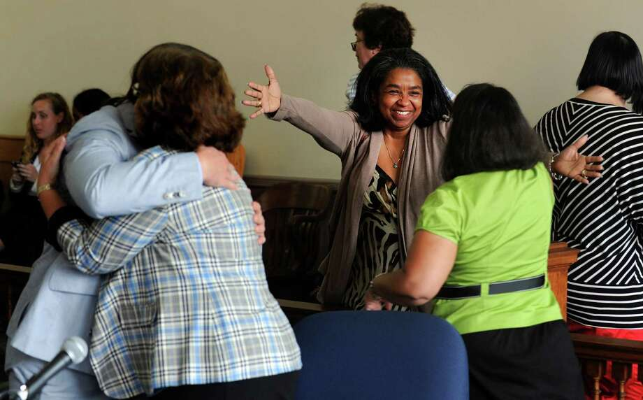 Kevin Smith and plaintiff Carmen Lopez, left, hug, as Board of Education member Sauda Baraka opens her arms to co-plaintiff Debbie Reyes-Williams after Judge Barbara Bellis ruled to dissolve the stay that was keeping Paul Vallas in his position as superintendent pending an appea Wednesday, July 10, 2013 in Bridgeport Superior Court. Photo: Autumn Driscoll / Connecticut Post