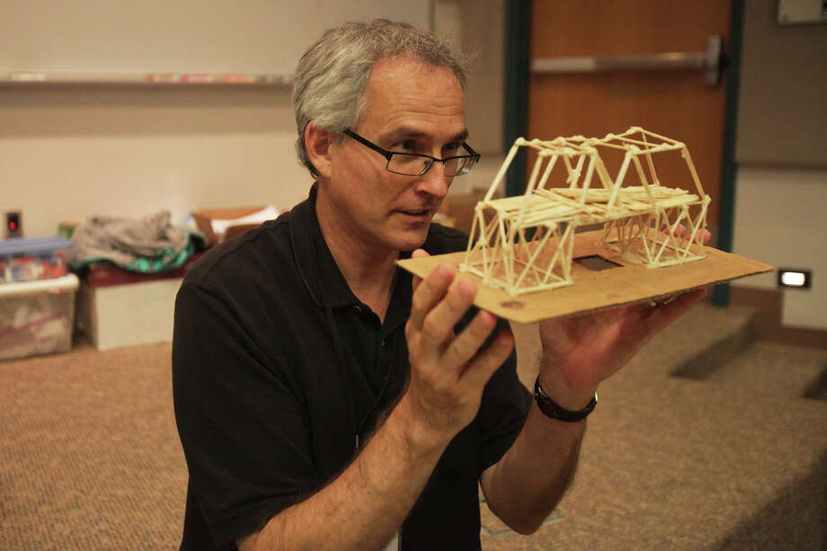 Jim Reeves of San Antonio, PREP instructor, inspects a bridge made from approximately 200 toothpicks during the San Antonio Prefreshman Engineering Program at UTSA's downtown campus on Wednesday, July 10, 2013. Students were divided into groups of two and given about 200 toothpicks as well as a small bottle of Elmer's Glue and a small bottle of wood glue. The bridges were tested to see if they could hold at least 20 pounds, if a scale truck could fit across it and if a scale boat could fit under it. The students spent about two days outside of the camp building the bridges. Photo: Abbey Oldham, San Antonio Express-News / © San Antonio Express-News