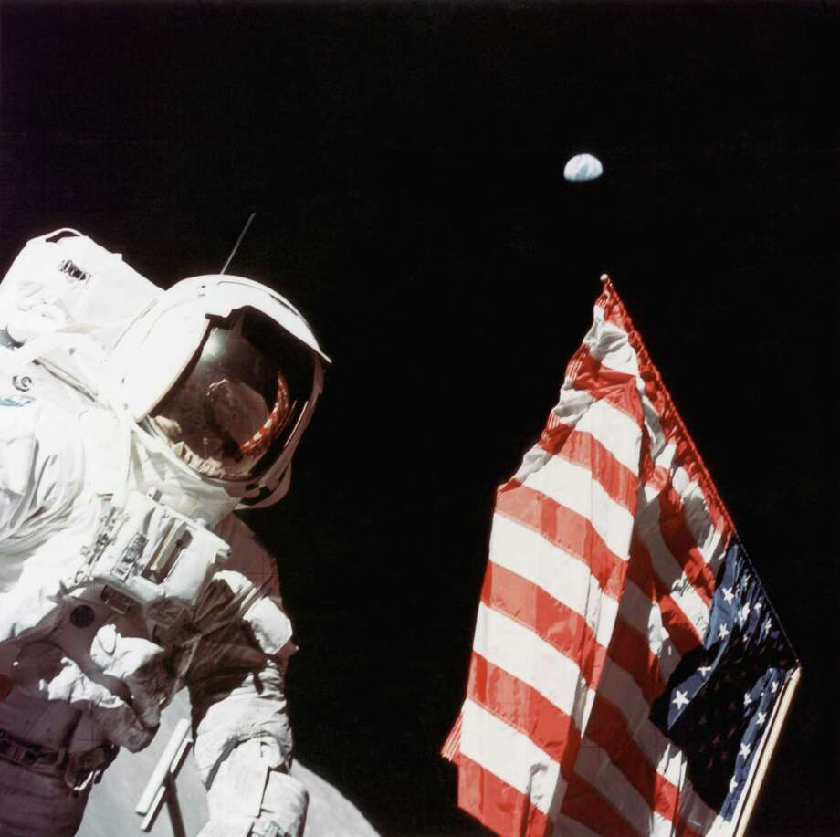 American geologist and Apollo 17 astronaut Harrison Hagan Schmitt stands next to the American flag on the surface of the moon, at the Taurus-Littrow landing site, in December 1972. Earth is visible in the far distance. Photo: Space Frontiers, Getty Images / 2007 Getty Images