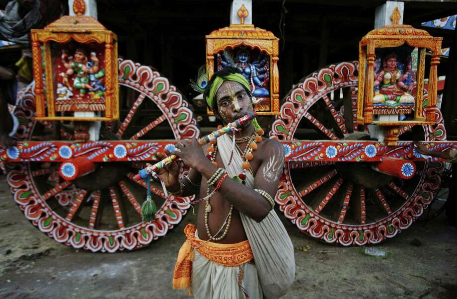 A devotee dressed as Lord Krishna plays the flute ahead of a Jagannath Ratha-yatra (chariot procession) during the annual festival in India. Photo: Biswaranjan Rout, STR / AP