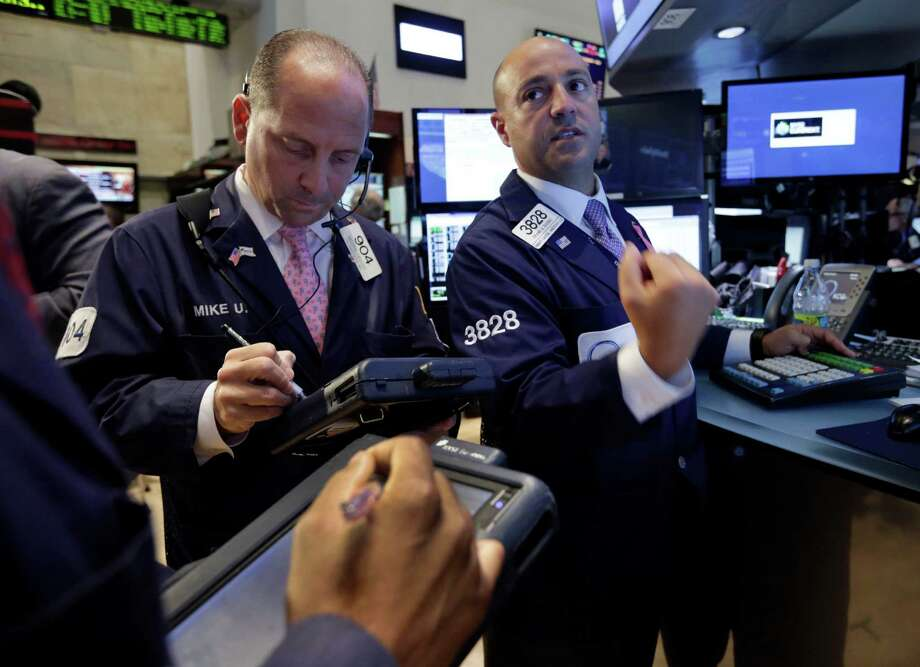Specialist Frank Babino, right, and trader Michael Urkonis works on the floor of the New York Stock Exchange Wednesday, July 10, 2013. Stocks nudged higher in early trading Wednesday before the Federal Reserve releases minutes from its most recent meeting. (AP Photo/Richard Drew) ORG XMIT: NYRD101 Photo: Richard Drew / AP