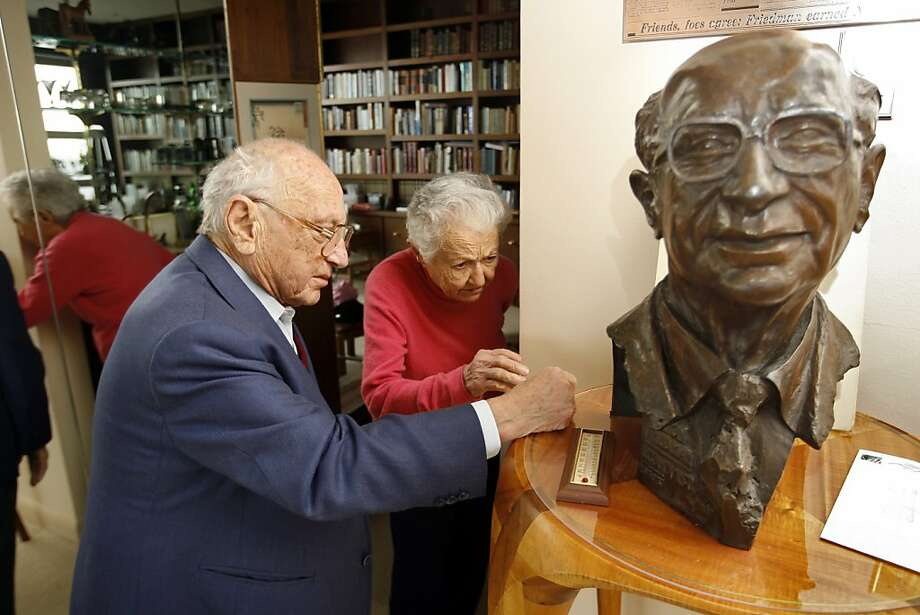 Economist Milton Friedman, who promoted the idea that the marketplace advances the best interests of society, looks at his bust with his wife, Rose, in S.F. in 2006. Photo: Chris Stewart, SFC