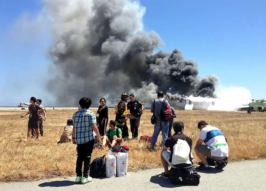 In this Saturday, July 6, 2013, photo provided by passenger Benjamin Levy, passengers from Asiana Airlines flight 214, many with their luggage, on the tarmac just moments after the plane crashed at the San Francisco International Airport in San Francisco. The flight crashed upon landing, and two of the 307 passengers aboard were killed. Photo: Benjamin Levy, Associated Press