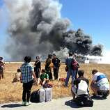 In this Saturday, July 6, 2013, photo provided by passenger Benjamin Levy, passengers from Asiana Airlines flight 214, many with their luggage, on the tarmac just moments after the plane crashed at the San Francisco International Airport in San Francisco. The flight crashed upon landing, and two of the 307 passengers aboard were killed.
