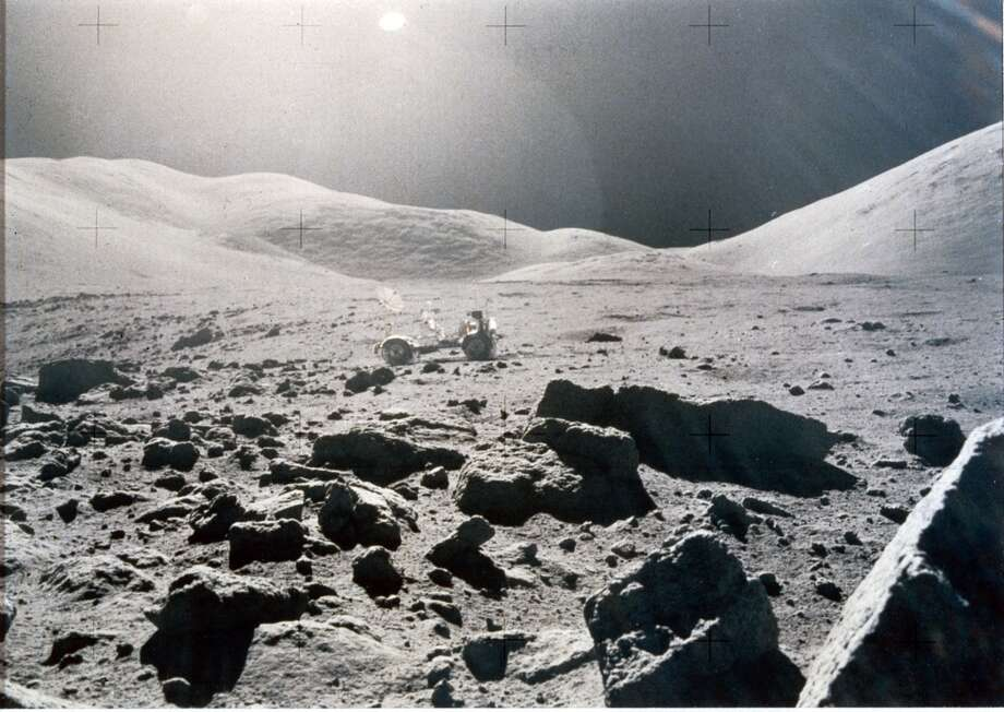 A rock-strewn landscape with the Lunar Rover and rolling hills in the background is shown in this photo from Apollo 15. Photo: Science & Society Picture Library Via Getty Images