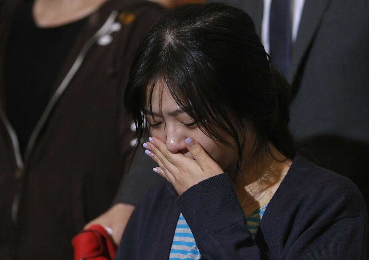 An unidentified flight attendant, injured in Saturday's crash of Asiana Airlines Flight 214, cries during a brief news conference at SFO in San Francisco, Calif. on Wednesday, July 10, 2013.