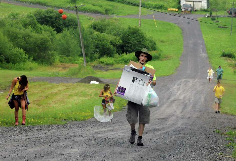 Camp Bisco volunteer Tim Berento of Kerhonkson carries personal supplies into the concert site Wednesday afternoon, July 10, 2013, in Pattersonville, N.Y. The concert starts Thursday. (Michael P. Farrell/Times Union) Photo: Michael P. Farrell / 00023099A