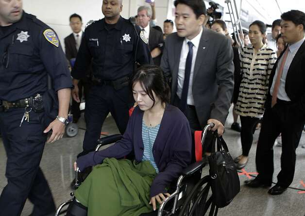 An unidentified flight attendant injured in Saturday's crash of Asiana Airlines Flight 214 is escorted to a brief news conference at SFO in San Francisco, Calif. on Wednesday, July 10, 2013. Photo: Paul Chinn, The Chronicle