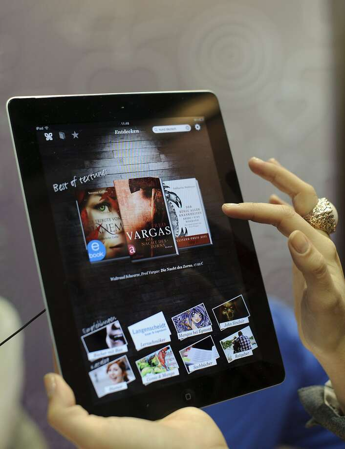 "(FILES) A fair goer tries out the textunes eBook reader app on an Apple iPad at the Leipzig Book Fair in this March 15, 2012 file photo on the fairgrounds in Leipzig, eastern Germany.  Apple on July 10, 2013 rejected a judge's ruling that it conspired with publishers to raise the price of e-books, and said it would appeal the decision. ""Apple did not conspire to fix e-book pricing and we will continue to fight against these false accusations,"" an Apple spokesman said after Judge Denise Cote's ruling. ""We've done nothing wrong and we will appeal the judge's decision."" AFP PHOTO / ROBERT MICHAELROBERT MICHAEL/AFP/Getty Images Photo: Robert Michael, AFP/Getty Images"
