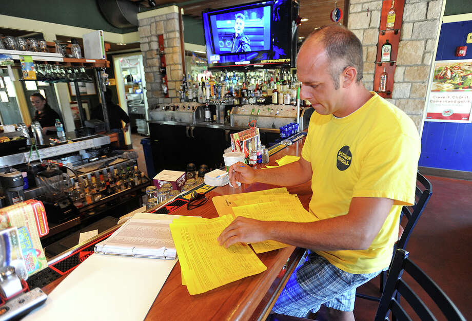 Jeremy Doucett counts signatures on a petition at the Silsbee Chili's bar Wednesday. The petition requests a measure on the November ballot that will help remove an ordinance requiring area eateries to pay a $20,000 annual fee to sell mixed beverages. Doucett said the  Photo taken Wednesday, July 10, 2013 Guiseppe Barranco/The Enterprise Photo: Guiseppe Barranco, STAFF PHOTOGRAPHER / The Beaumont Enterprise