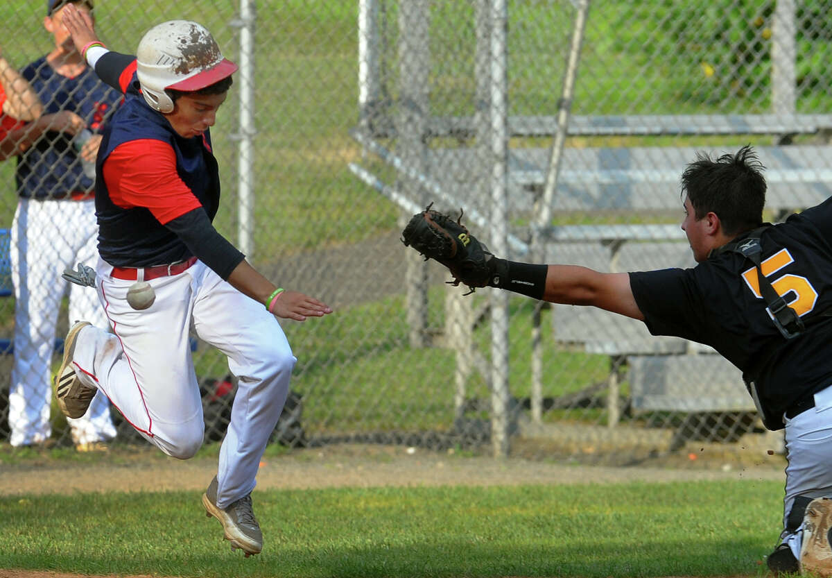 Trumbull catcher Chris DiCocco tries to tag out Norwalk's Jesse Rodriguez, left, as he heads to home plate, during Babe Ruth little league baseball action at Tunxis Hill Park in Fairfield, Conn. on Wednesday July 10, 2013.