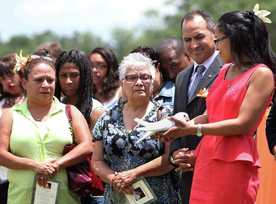 """Kischa Hernandez holds a dove right before it's release in honor of foster child Lee'Ona """"Lilly"""" Ramirez during a memorial service at Brookside Funeral Home on Wednesday, July 10, 2013, in Houston. Photo: Mayra Beltran / © 2013 Houston Chronicle"""
