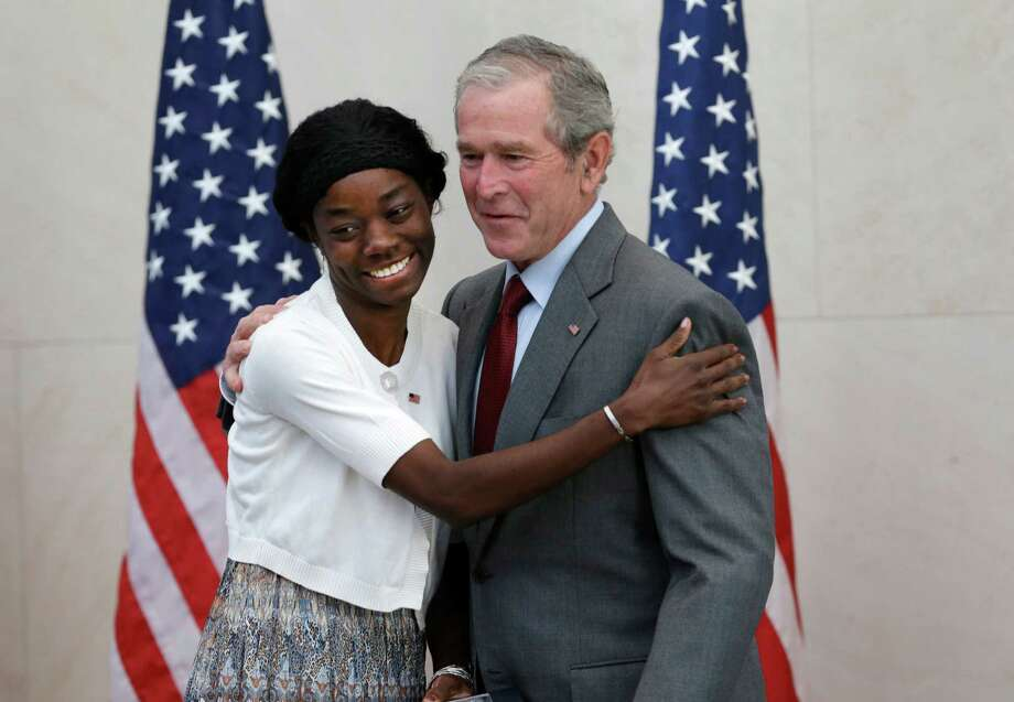 Former President George W. Bush, right, posses for a photo with Mondell Bernadette Avril after she was sworn in as a U.S. citizen during a ceremony at the The George W. Bush Presidential Center in Dallas, Wednesday, July 10, 2013. Twenty new citizens took the oath of U.S. citizenship at the former president's library.  (AP Photo/LM Otero) ORG XMIT: TXMO102 Photo: LM Otero / AP