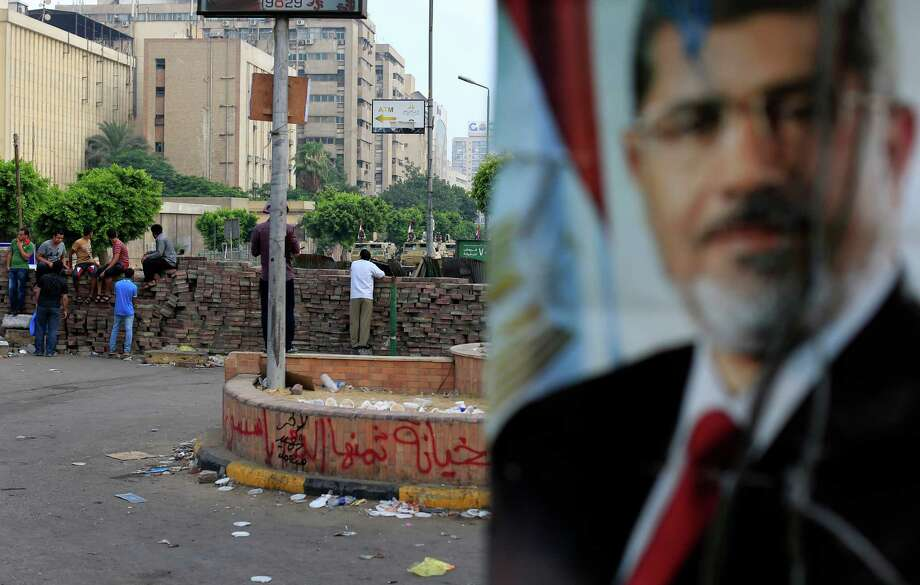 Supporters of ousted President Mohammed Morsi protest as army soldiers guard at the Republican Guard building in Nasr City, in Cairo, Egypt, Wednesday, July 10, 2013. (AP Photo/Hassan Ammar) ORG XMIT: HAS109 Photo: Hassan Ammar / AP