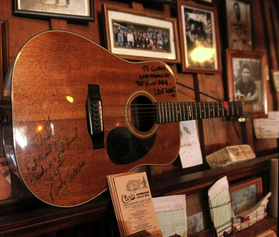 "Clark's Outpost is one of the Tioga, Texas, businesses that is a favorite for country star Randy Travis, who lives nearby.  A guitar signed by both Lyle Lovett (top right) and by Travis (lower left, with a special message including ""Great to meet you, Thanks for a great lunch"") are shown in the BBQ restaurant in 2012.   (Mona Reeder/The Dallas Morning News) Photo: Mona Reeder, Staff Photographer / The Dallas Morning News"