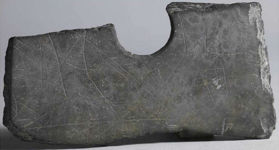Archaeologists say markings etched on a piece of a stone ax unearthed in Pinghu, in eastern China's Zhejiang province, may be a newly discovered form of primitive writing. Photo: Associated Press