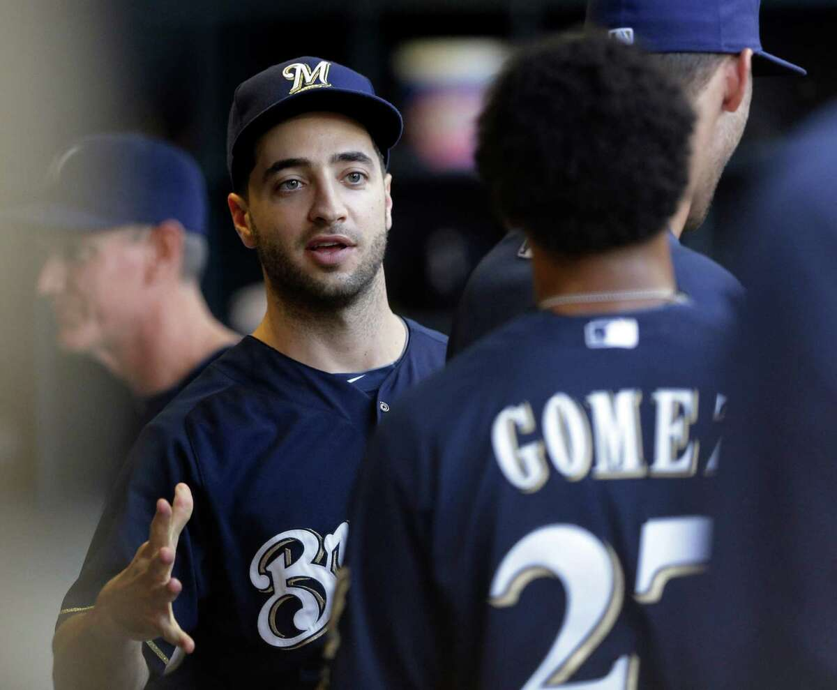 Milwaukee Brewers' Ryan Braun is welcomed back in the dugout by teammate Carlos Gomez before a baseball game against the Cincinnati Reds Tuesday, July 9, 2013, in Milwaukee. (AP Photo/Morry Gash) ORG XMIT: WIMG101