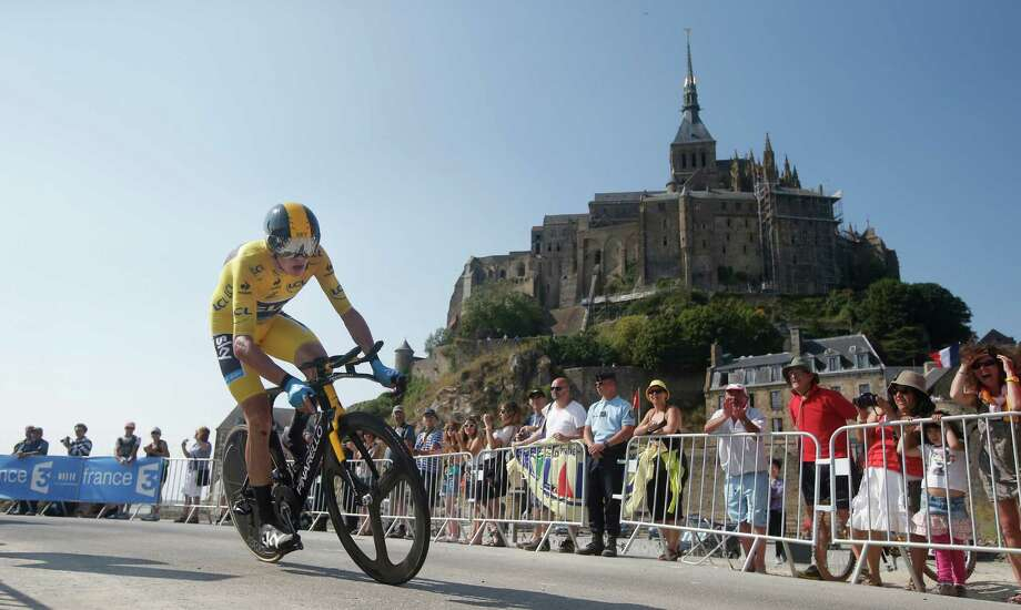 Christopher Froome of Britain, wearing the overall leader's yellow jersey, passes world heritage site Mont-Saint-Michel, rear, a rocky tidal island which holds a monastery, during the eleventh stage of the Tour de France cycling race, an individual time trial over 33 kilometers (20.6 miles) with start in in Avranches and finish in Mont-Saint-Michel, western France, Wednesday July 10 2013. (AP Photo/Laurent Cipriani) ORG XMIT: PDJ177 Photo: Laurent Cipriani / AP