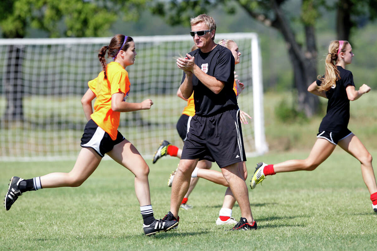 Lions FC '96 coach Peter Moore (center) works with the team during a practice session at Lions Pride Park on Tuesday, July 2, 2013.