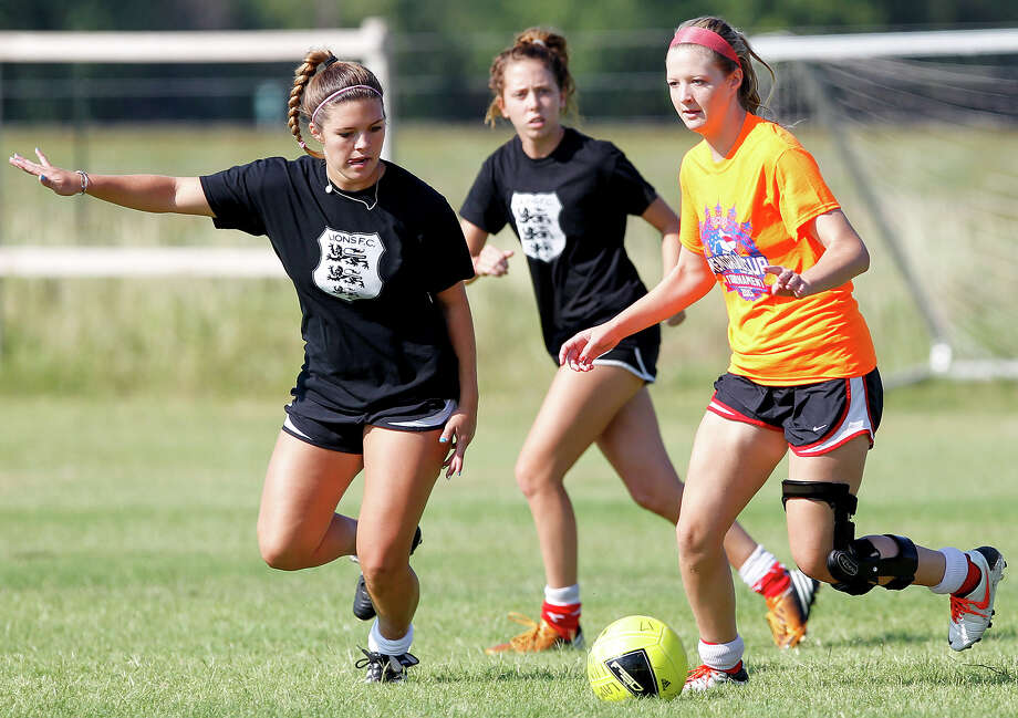 Danielle Struxness (from right) tries to drive the ball past Kayle Nagle and Lorin Burton during a Lions FC '96 practice session at Lions Pride Park on Tuesday, July 2, 2013.  Photo: Marvin Pfeiffer, San Antonio Express-News / Express-News 2013