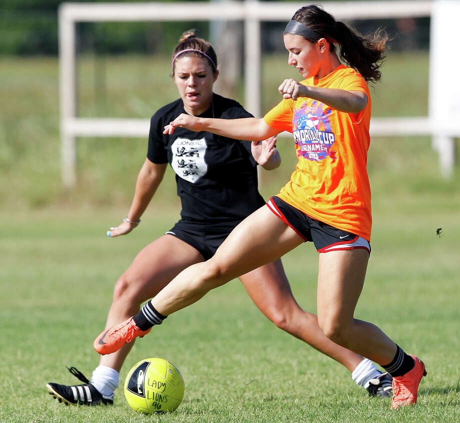 Rachel Gurinsky (right) tries to drive the ball past Lorin Burton during a Lions FC '96 practice session at Lions Pride Park  on Tuesday, July 2, 2013. Photo: Marvin Pfeiffer, San Antonio Express-News / Express-News 2013