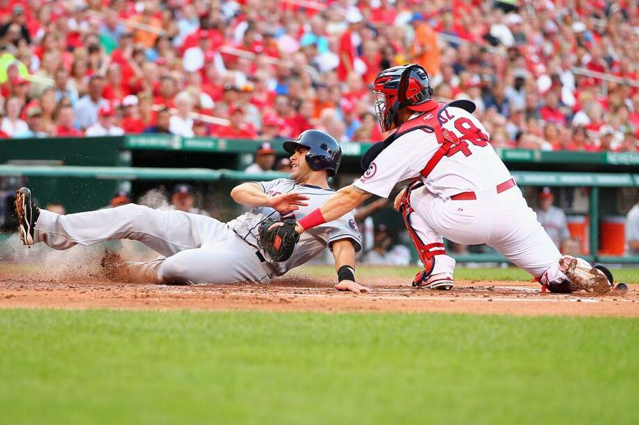 July 10: Cardinals 5, Astros 4 J.D. Martinez is tagged out at home by Tony Cruz of the Cardinals.