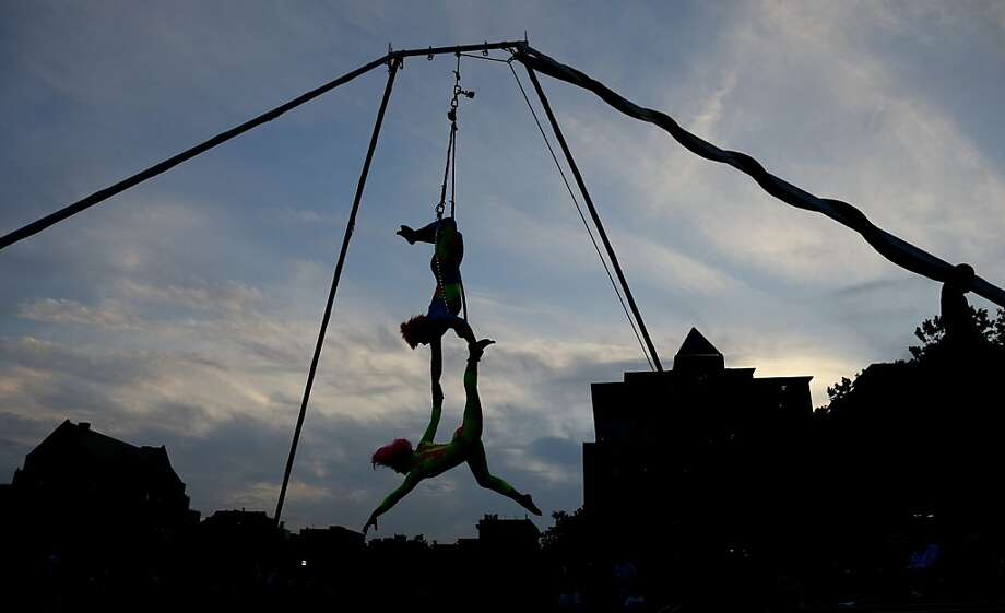 Performers hang during a public show at Pier A Park, Wednesday, July 10, 2013, in Hoboken, N.J. (AP Photo/Julio Cortez) Photo: Julio Cortez, Associated Press