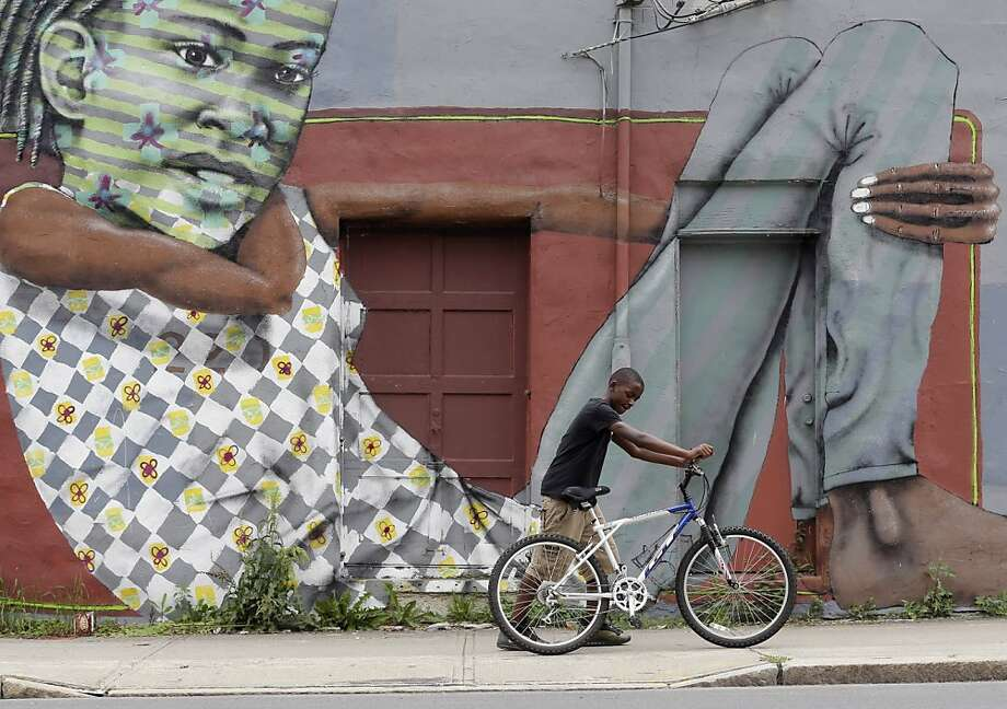 A youngster pushes his bicycle past a mural in the South End neighborhood on Wednesday, July 10, 2013, in Albany, N.Y.  (AP Photo/Mike Groll) Photo: Mike Groll, Associated Press