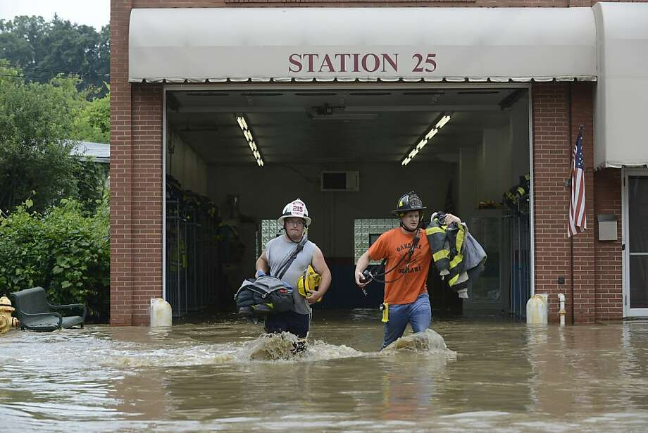 Oakdale Firefighters Mike Hartman, left, and Luke Navickas, right, rescue gear from their fire station as water floods it in Oakdale, Pa.,  on Wednesday, July 10, 2013. The city and its southern suburbs were cleaning up from flash flooding caused by heavy morning rains and bracing for more of the same with additional storms forecast for the region later Wednesday. (AP Photo/Tribune Review, Justin Merriman) Photo: Justin Merriman, Associated Press