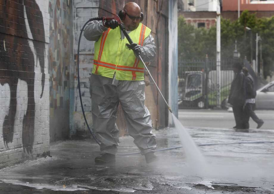 Stephen Lee, from the Department of Public Works, power washes a sidewalk on Jessie Street near Sixth Street in San Francisco, Calif. on Wednesday, July 10, 2013.