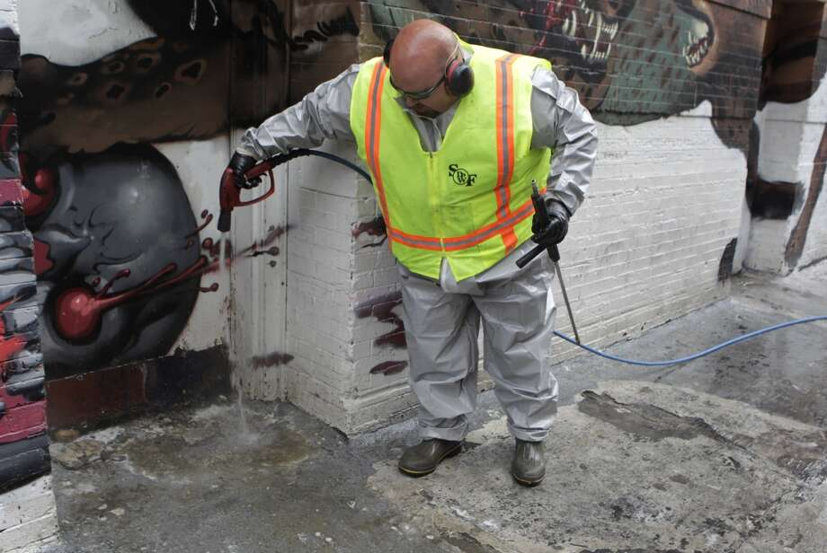 Stephen Lee, from the Department of Public Works, applies disinfectant to a particularly contaminated doorway on Jessie Street near Sixth Street in San Francisco, Calif. on Wednesday, July 10, 2013.