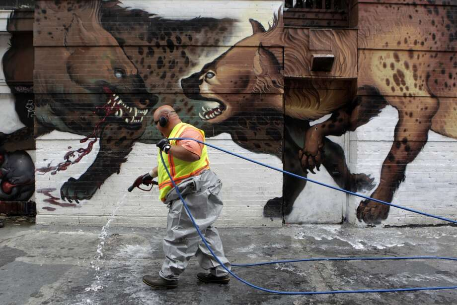 Stephen Lee, from the Department of Public Works, sprays a disinfectant before steam cleaning a sidewalk on Jessie Street near Sixth Street in San Francisco, Calif. on Wednesday, July 10, 2013.