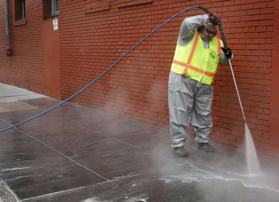 Stephen Lee, from the Department of Public Works, steam cleans a sidewalk on Jessie Street near Sixth Street in San Francisco, Calif. on Wednesday, July 10, 2013.