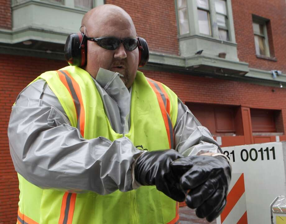 Stephen Lee, from the Department of Public Works, dons hazmat gear before steam cleaning a sidewalk on Jessie Street near Sixth Street in San Francisco, Calif. on Wednesday, July 10, 2013.