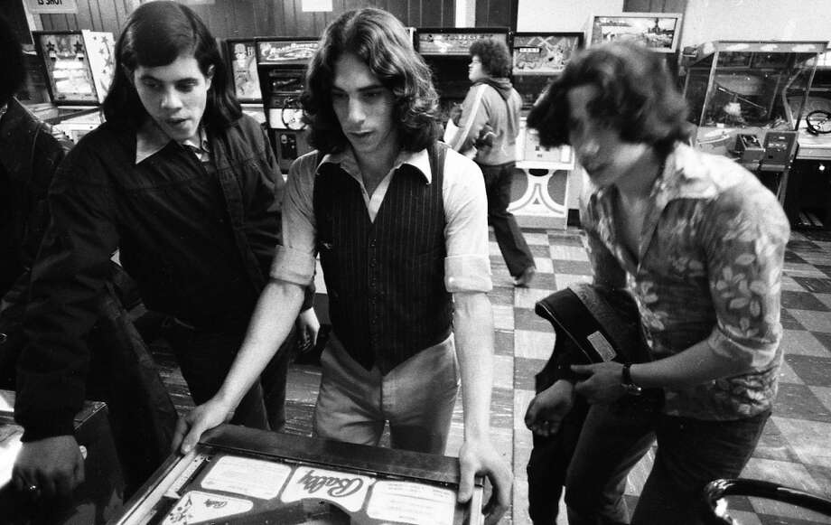 Jan. 28, 1977: I have no proof that this is Tim Lincecum's dad playing pinball in 1977, but it has to be, right? Note all the cool 1970s arcade games behind this awesome trio.