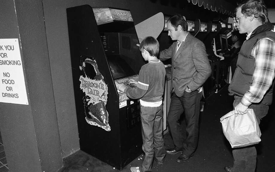 Dec. 10, 1983: Father and son get their mind blown by Dragon's Lair, while a creepy looking dude with a paper sack watches. The game looked amazing, but this was the beginning of the end for arcades.
