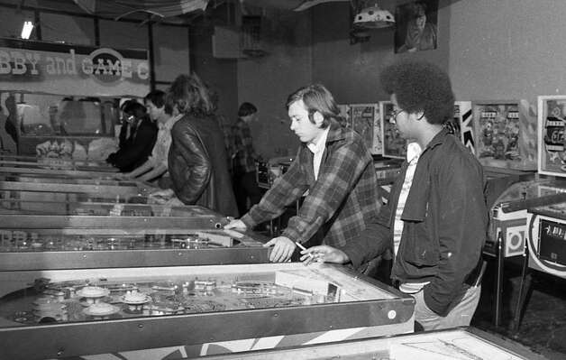 Nov. 27, 1974: Pinball enthusiast enjoying a parlor in Berkeley, back when you could smoke in a place where children convened. I love the random poster of a tiger on the upper right.
