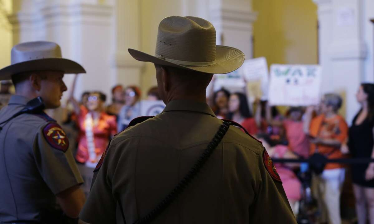 Texas state troopers stand in the Capitol rotunda as they watch opponents of HB 2, an abortion bill, after the Texas House made their final vote, Wednesday, July 10, 2013, in Austin, Texas. The approved bill, which now goes to the Texas Senate, would require doctors to have admitting privileges at nearby hospitals, only allow abortions in surgical centers, dictate when abortion pills are taken and ban abortions after 20 weeks. (AP Photo/Eric Gay)