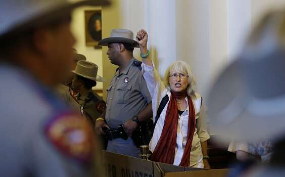 Hope Phillips, and opponent of HB 2, an abortion bill, yells with others outside the Texas House after the final vote, Wednesday, July 10, 2013, in Austin, Texas. The bill, which now goes to the Texas Senate,  would require doctors to have admitting privileges at nearby hospitals, only allow abortions in surgical centers, dictate when abortion pills are taken and ban abortions after 20 weeks. (AP Photo/Eric Gay) Photo: Associated Press