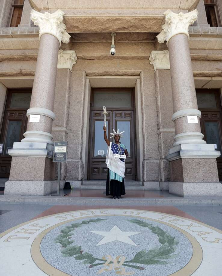Peace Washington stands outside the Texas Capitol dress as the Statute of Liberty, Wednesday, July 10, 2013, in Austin, Texas. The Texas House approved HB 2 with a third and final vote Wednesday, which would require doctors to have admitting privileges at nearby hospitals, only allow abortions in surgical centers, dictate when abortion pills are taken and ban abortions after 20 weeks. (AP Photo/Eric Gay) Photo: Associated Press