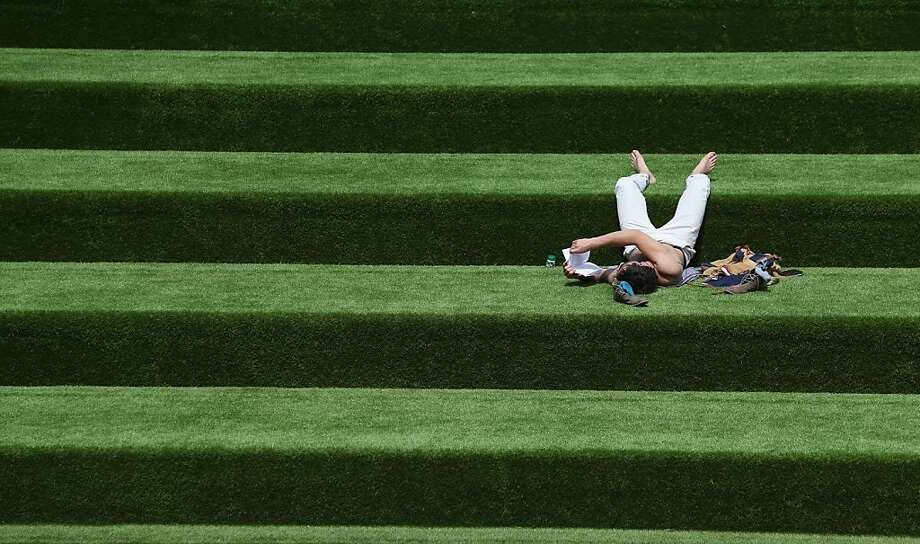 A Brit catches up on his reading on steps of artificial turf in London. Photo: Oli Scarff, Getty Images