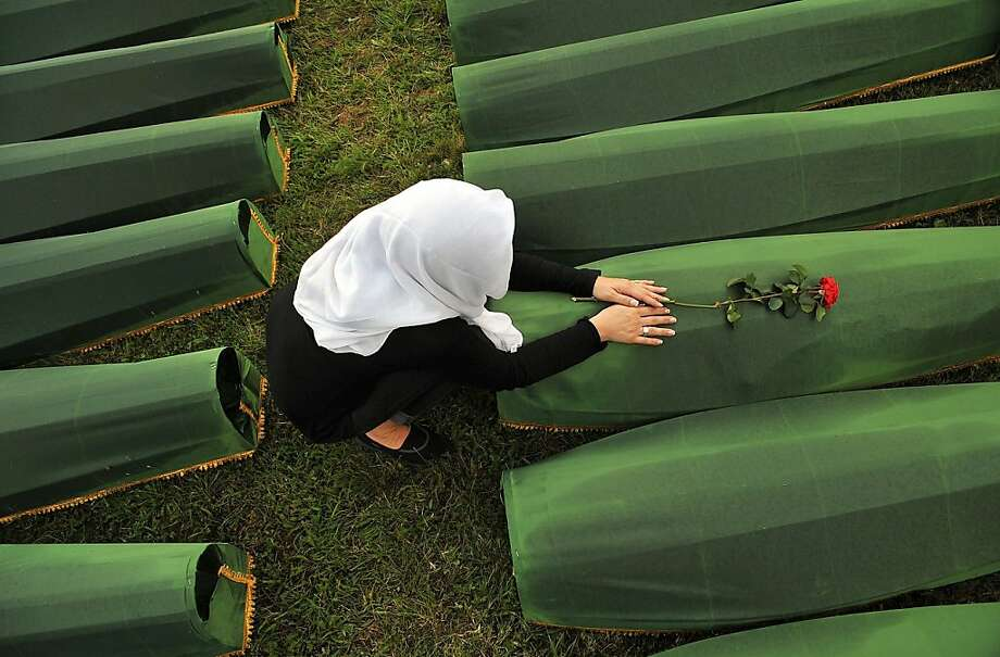 Eighteen years of grieving:A survivor of Srebrenica Massacre mourns over the casket of a loved one at Memorial Cemetery 