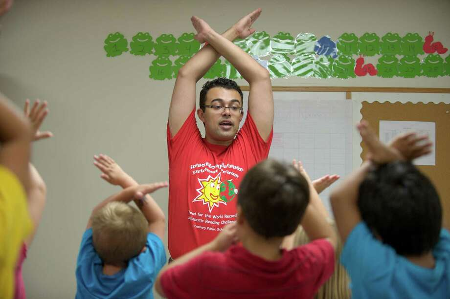 "Instructor Hans Guardado leads the class in the ""alphabet stretch"" where they make the shapes of the letters in the alphabet, during the OWL Club. It is part of the Sunsational Summer Enrichment Program by the Danbury Public Schools and is meant to prevent summer learning loss by students. The program takes place at Rogers Middle School, in Danbury Conn. Thursday July 11, 2013. Photo: H John Voorhees III"