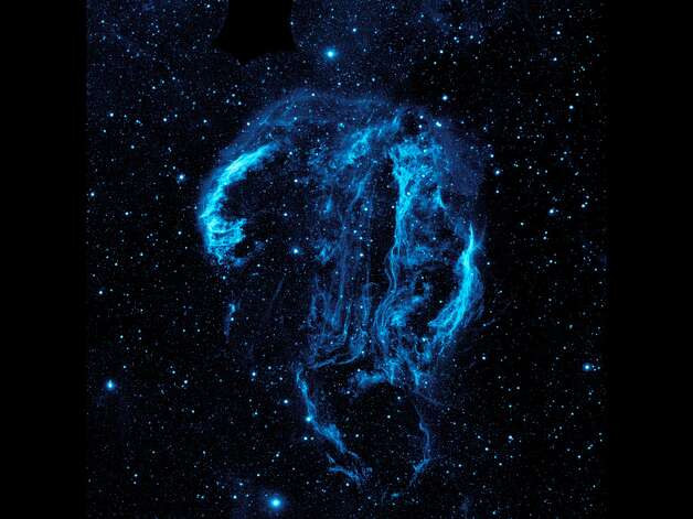 This image from NASA's Galaxy Evolution Explorer shWispy tendrils of hot dust and gas glow brightly in this ultraviolet image of the Cygnus Loop nebula, taken by NASA's Galaxy Evolution Explorer. The nebula lies about 1,500 light-years away, and is a supernova remnant, left over from a massive stellar explosion that occurred between 5,000 to 8,000 years ago. The Cygnus Loop extends over three ti
