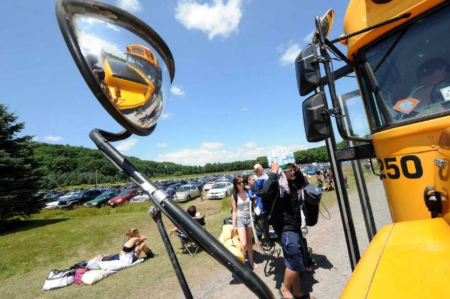 Concertgoers line up to catch the bus to Camp Bisco, the four-day music festival that starts Thursday in Duanesburg. (Michael P. Farrell / Times Union)
